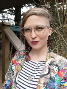 Baylee smiles with her lips together and her pink/blonde hair in a braid. The left side of her head is shaved, and she wears gold cat eye glasses with a rainbow blazer.