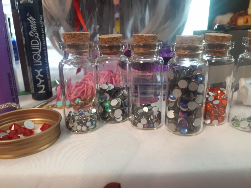 Five small glass bottles filled with rhinestones.