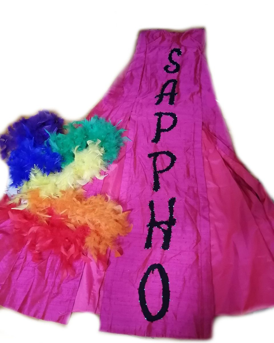 A long, thin bright pink gown with 'Sappho' written down the front in large, black, rhinestoned letters. A rainbow feather fan lies to the lower left.