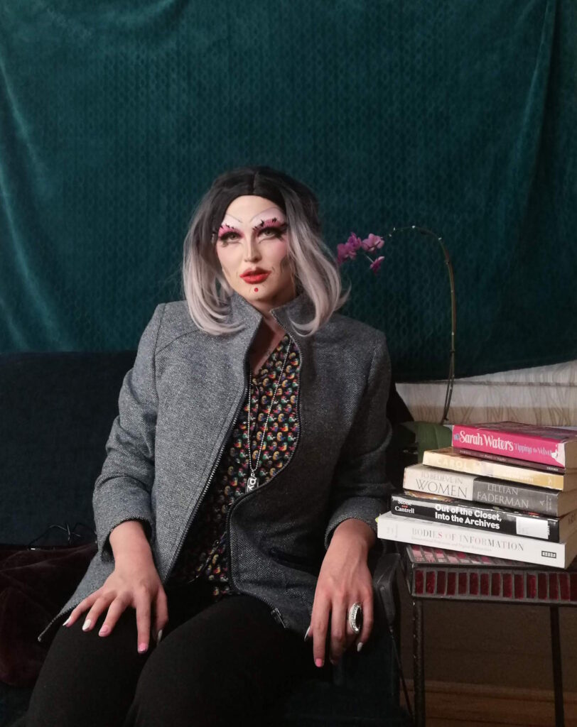 "A femme drag performer in a black and grey wig sits formally dressed beside a purple orchid and a stack of lesbian books including ""Tipping the Velvet"" by Sarah Waters and ""To Believe in Women"" by Lillian Faderman."