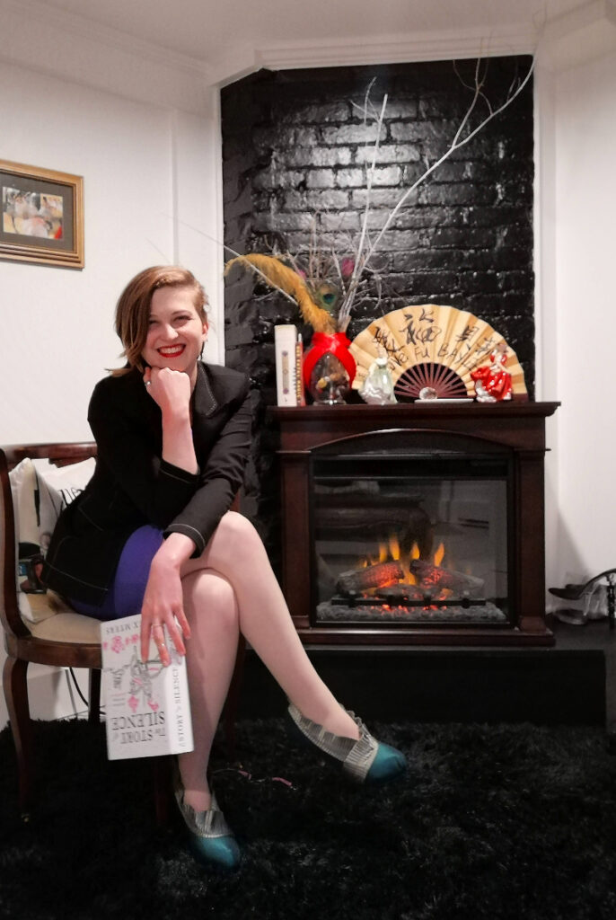 """Baylee sits in an antique wooden chair in front of a black brick fireplace holding """"The Story of Silence"""" novel. She has her legs crossed, her chin propped on her right hand, and is smiling widely."""